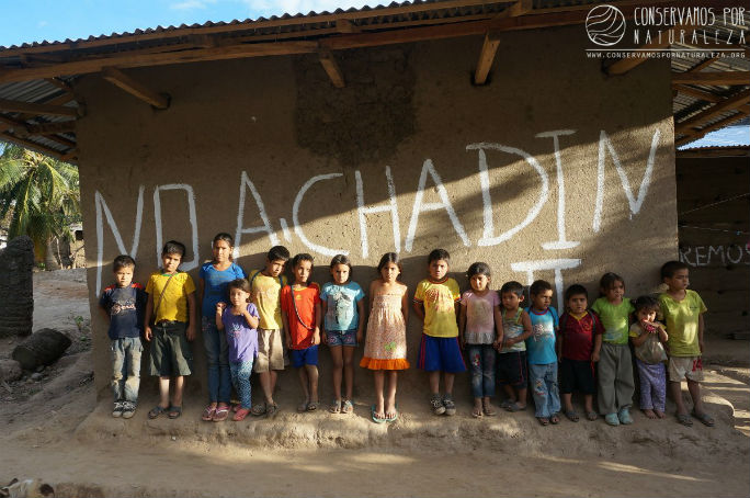 "Children of Mendán standing in front of the message ""No a Chadin II"" painted on one of the houses. Chadin II dam will flood their homelands. This will be one of the first communities to be inundated by the filling of the Chadin Dos reservoir/dam."