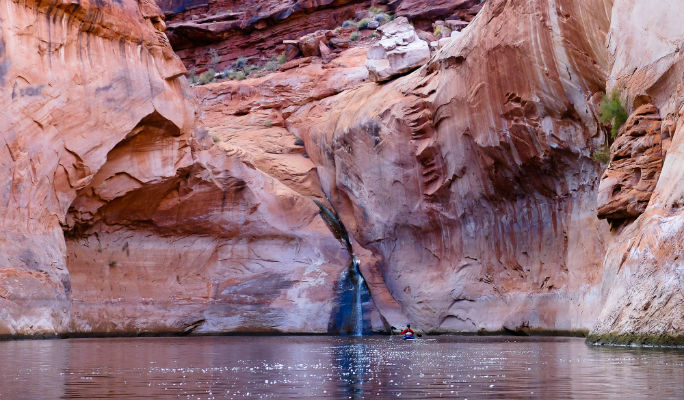 """In Long Canyon, Kalen and Hilary discover a small waterfall that I had overlooked. To excited calls of """"Hey, come down here—waterfall!"""" I come around corner to see Hilary gliding up to its base. Unexpected treasures still exist in this impacted landscape."""